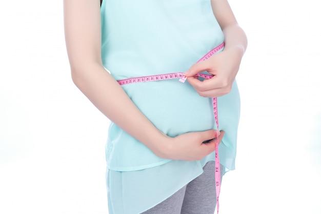De zwangere vrouw meet haar buik door meetlint