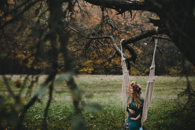 De zwangere vrouw rust buiten op de kabelschommeling het hangen