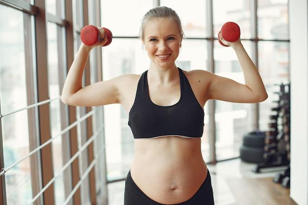 De zwangere vrouw speelt sporten met dambbels