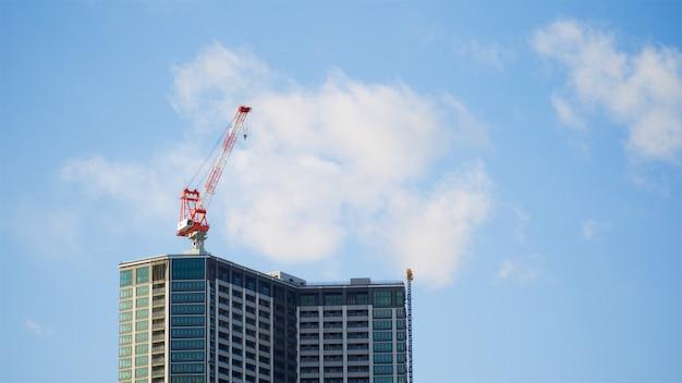De zware materiaalkraan over wolkenkrabberbouwterrein in heldere blauwe hemel en wolk op de ochtenddag, gebruikt voor lift en vervoert voorwerp naar de plaats