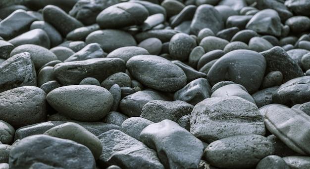 De zwarte achtergrond van de kiezelstenensteen met selectieve nadruk