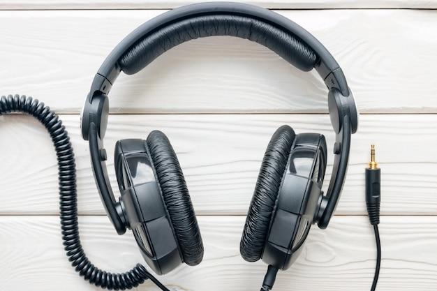 De zwarte hoofdtelefoons sluiten omhoog op een witte achtergrond