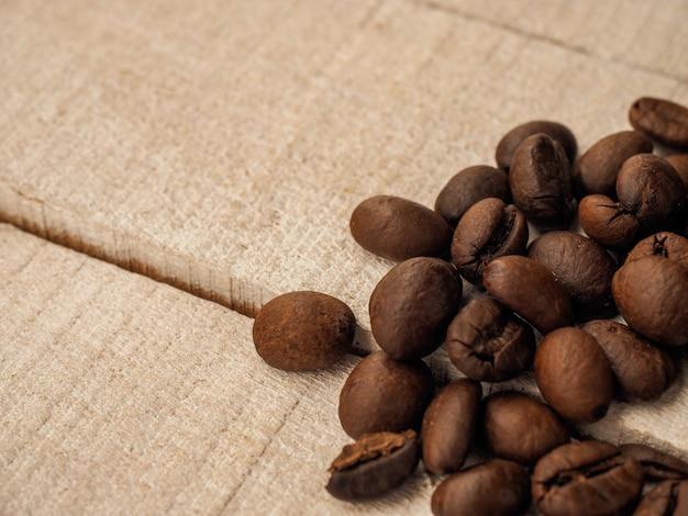 De zwarte koffiebonen liggen op lichte houten lijst, achtergrond. plaats voor tekst