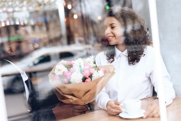 De zwarte man kwam op een date naar een meisje in een café.