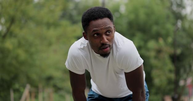 De zwarte man stopte na het joggen in het bospark moe uitgeput besloten rust na de training