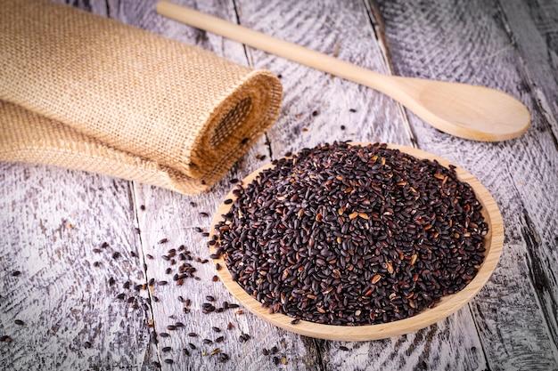 De zwarte rijst op oude houten tafel. selectieve aandacht