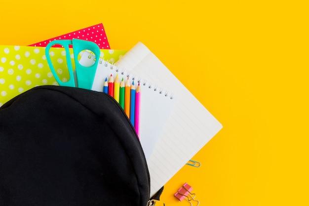 De zwarte rugzak en schoollevering op een gele achtergrond met vlakke exemplaarruimte, lagen.