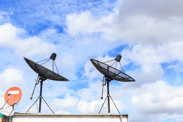 De zwarte satelliet installeert op het huisdak met blauwe hemelachtergrond