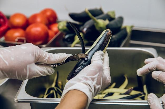 De zwarte schil van aubergines pellen
