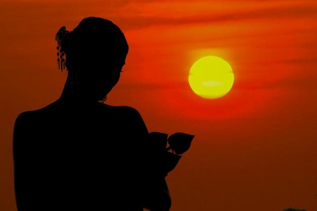 De zwarte silhouetvrouw die koesterend een lotusbloembloem bevinden zich bij zonsondergang