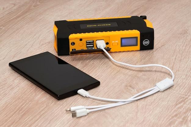 De zwarte smartphone is met een witte draad verbonden met een grote powerbank. detailopname