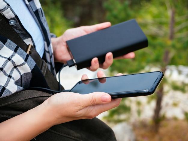 De zwarte smartphone is verbonden met de powerbank