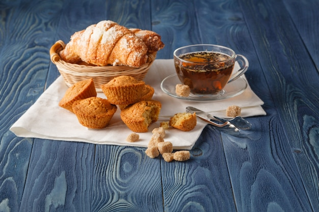 De zwarte thee van ceylon in glaskoppen, verse croissants, uitstekende houten achtergrond, selectieve nadruk