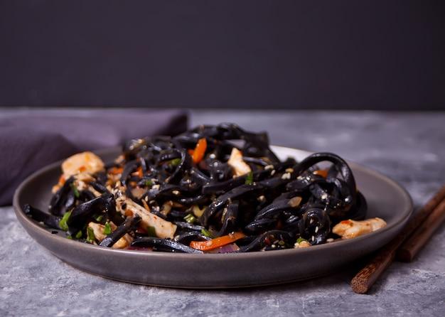 De zwarte udon noedels van de pijlinktvisinkt met kippenvlees op de zwarte plaat op donkere steenachtergrond.
