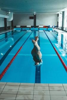 De zwemmer duwt zich van de rand van het zwembad af