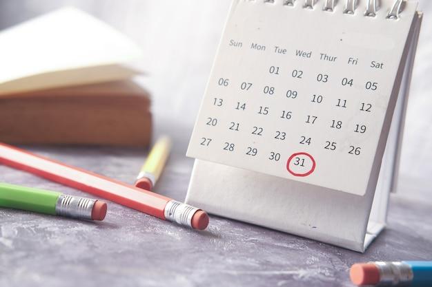 Deadline concept met rode markering op kalenderdatum met boek en potloden op tafel