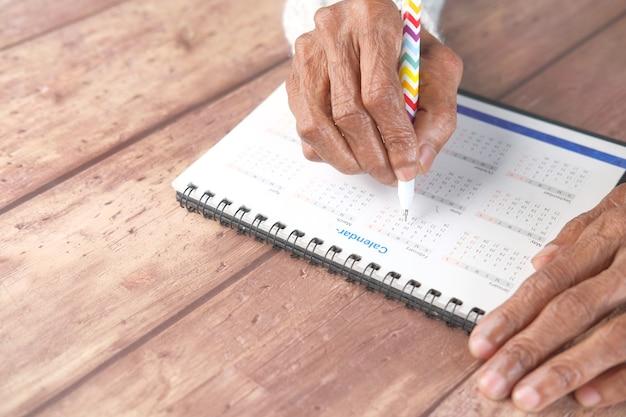 Deadline concept met senior vrouwen hand markering datum op kalender bovenaanzicht