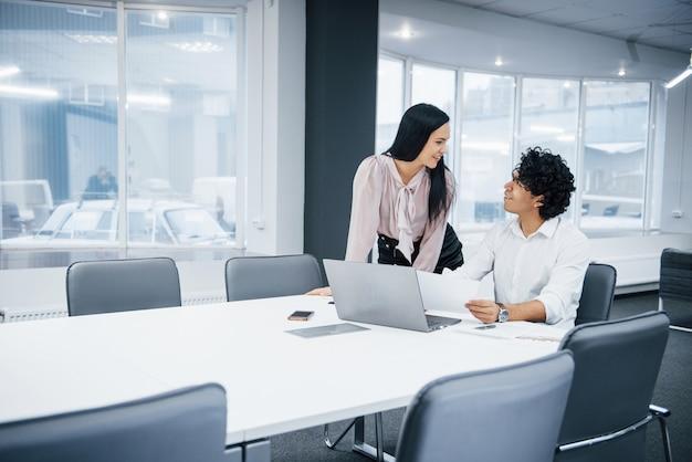 Deal tussen internationale mensen. vrolijke collega's in een modern kantoor glimlachen bij het doen van hun werk met behulp van laptop