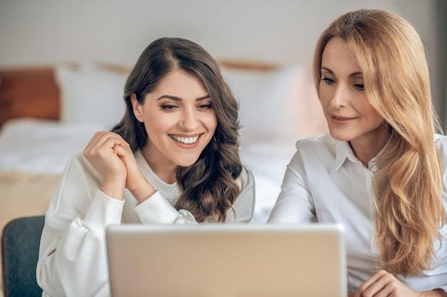 Deal. twee vrouwelijke collega's die de voorwaarden van een deal bespreken en er betrokken uitzien