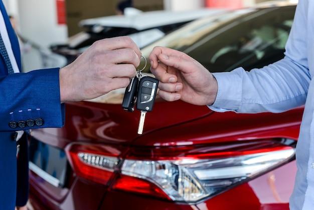 Dealer die sleutels geeft aan klant in showroom