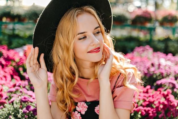 Debinair blanke vrouw poseren in frint van roze bloemen. nadenkend stijlvolle vrouw in hoed genieten van zomerdag.
