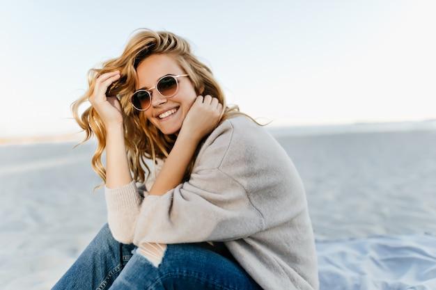 Debinair blinde vrouw zittend op zandstrand in herfst ochtend. openluchtportret van vrij krullende vrouw die in de zee glimlacht