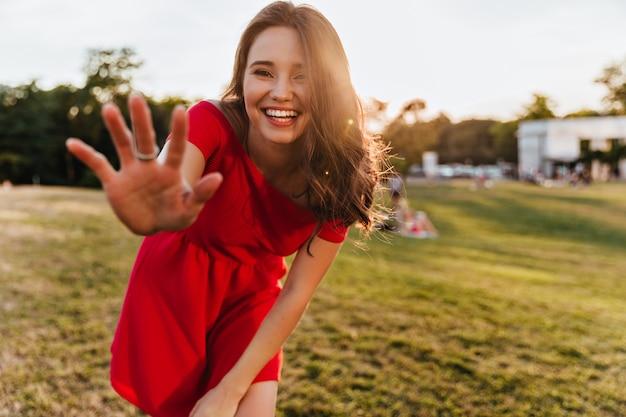 Debonair blanke vrouw die lacht naar camera in zonnige dag. buiten foto van vrolijk mooi meisje in een rode jurk staande in het park.