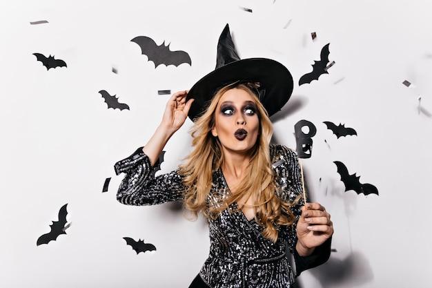 Debonair blonde vrouw in wizaed outfit. jocund krullend meisje gek rond in halloween.