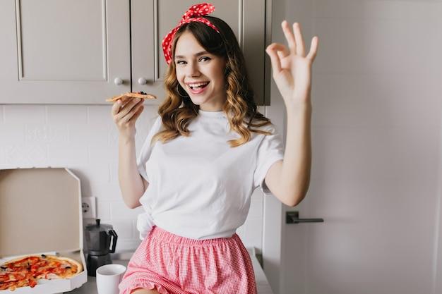 Debonair dame in schattige pyjama genieten van ontbijt. charmant vrouwelijk model dat met plezier pizza eet.