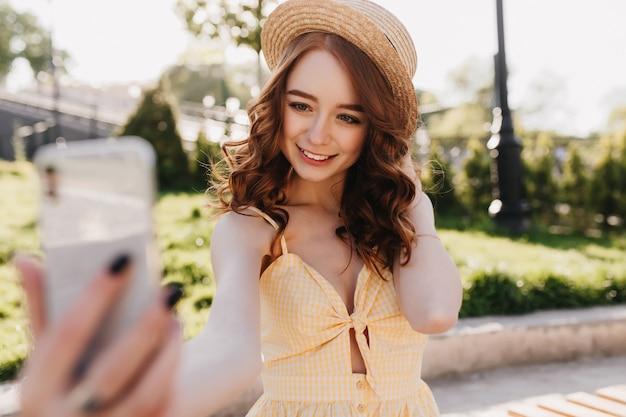 Debonair gember dame in hoed selfie maken in groen park. buitenfoto van fascinerende europese vrouw met rood haar die foto van zichzelf op aard neemt.