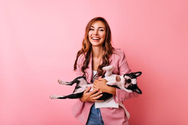 Debonair jonge vrouw in stijlvolle jas met grappige franse bulldog. portret van jocund langharige meisje tijd doorbrengen met haar hond.