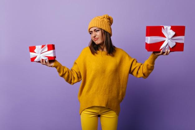 Debonair trendy meisje in gele kleren geschenken houden en gezichten trekken. indoor portret van prachtige brunette vrouw in casual kleding.
