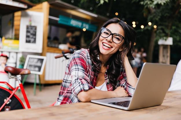 Debonair wit meisje in casual shirt poseren op straat met computer. openluchtportret van enthousiaste vrouwelijke student die laptop met behulp van.