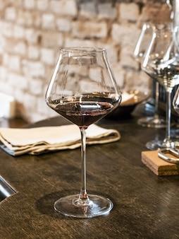 Decanteren van oude wijn. rode wijn in een glas op de balk.