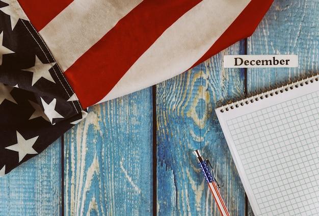 December-maand van kalenderjaar verenigde staten van amerika vlag van symbool van vrijheid en democratie met lege kladblok en pen op kantoor houten tafel