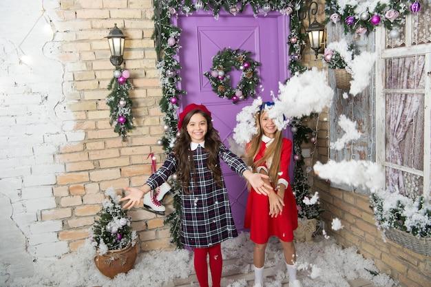 December plezier. kinderspelletjes op wintervakantie. kleine meisjes met kerstversiering. gelukkige kinderen vieren kerstmis en nieuwjaar. kleine kinderen gooien kunstmatige sneeuw. winter plezier.