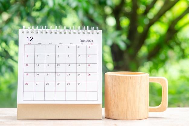 Decembermaand, kalenderbureau 2021 voor organisator tot planning en herinnering op houten tafel met groene natuurachtergrond.