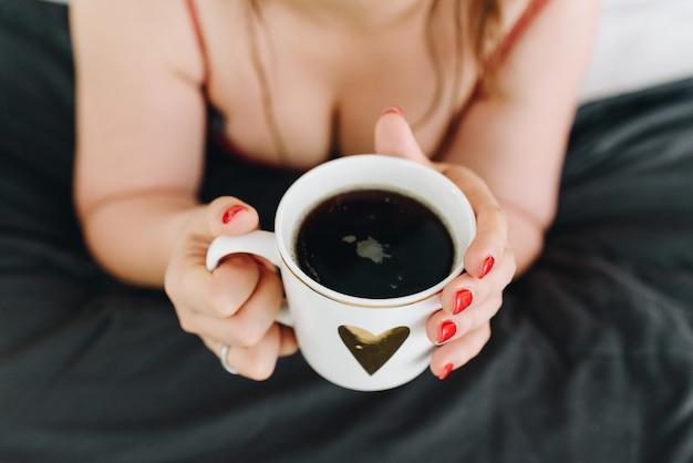 Decolleté of vrouwelijke borsten, jonge vrouw die een kop koffie drinkt