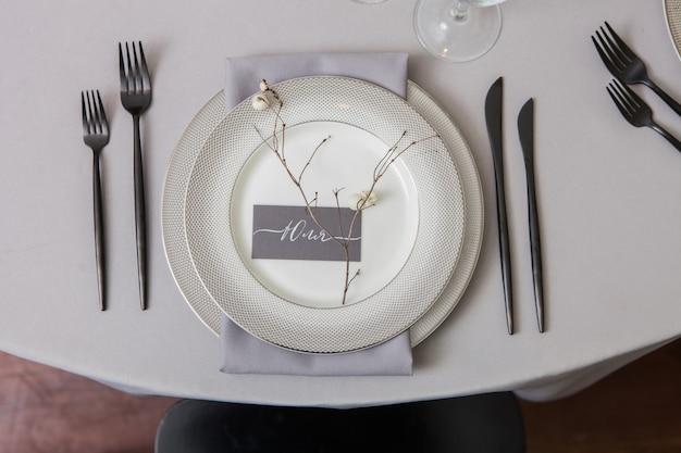 Decor bruiloftsdiner, gedekte tafel met bord, naamplaatje bruiloftskalligrafie vertaling uit het russisch - naam