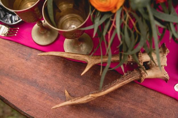 Decor. details. bruidsboeket. samenstelling. bruiloft decoraties. op de houten tafel in het bos staat een bloemstuk met rode, gele, roze bloemen en groen, kaarsen, beeldjes.
