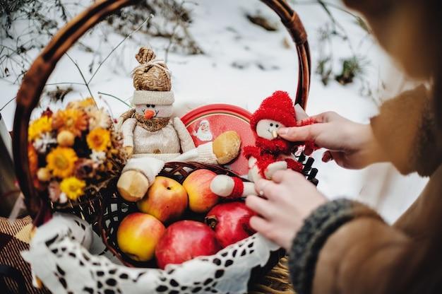 Decor op de sneeuw in het winterpark. mand met koekjes, fruit. gelukkig sneeuwpop op een deken op de picknick in het bos. prettige kerstdagen en nieuwjaarswenskaart met exemplaar-ruimte.