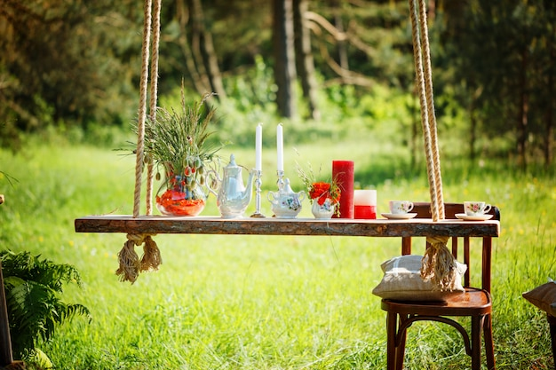 Decor romantisch diner met kaarsen, bloemen in groen bos tijdens prachtige zonsondergang.