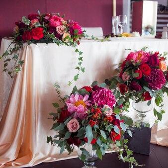 Decor van de pasgetrouwden. zijden tafelkleden, rode bloemen