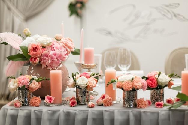 Decor voor de vakantie tafel. kandelaars met natuurlijke bloemen in roze kleuren.