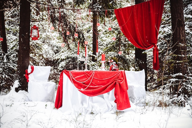 Decor voor een fotoshoot liefdesverhaal in het bos. romantische date op een ijzige besneeuwde dag. tafel en decoraties in het rood