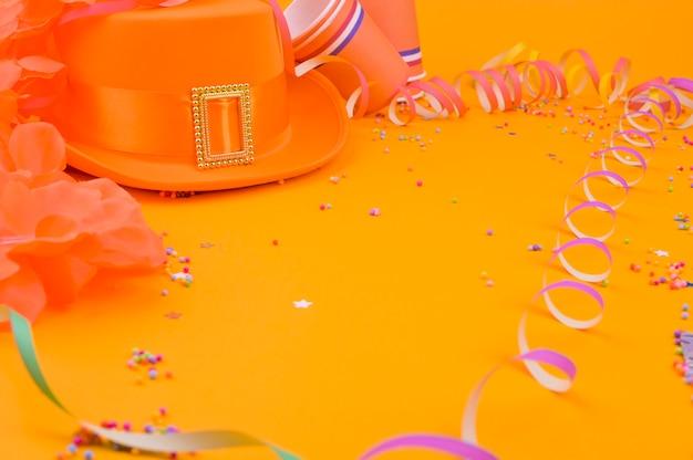 Decor voor een traditionele viering van koningsdag in nederland. carnaval-decoratie op een gele achtergrond. een vrije plek voor tekst. plat liggen.