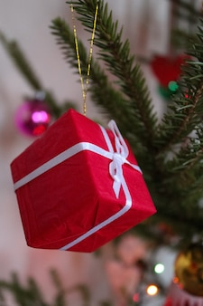 Decoratie in de vorm van een kleine geschenkdoos van wit rood met een rood lint op de kerstboom