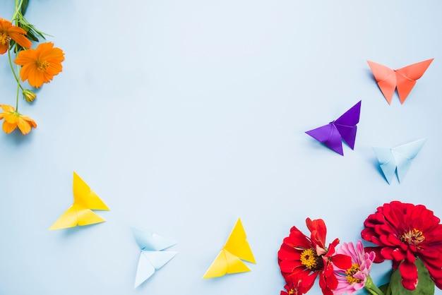 Decoratie met calendula goudsbloembloemen en origamidocument vlinders op blauwe achtergrond