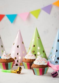 Decoratie met geglazuurde muffins en feestmutsen