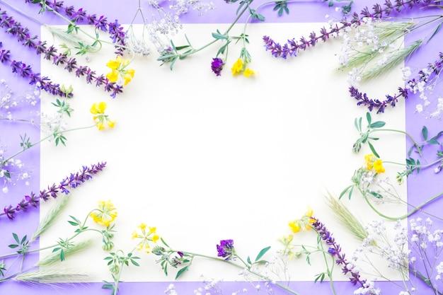Decoratie van bloemen op witboek over de paarse achtergrond